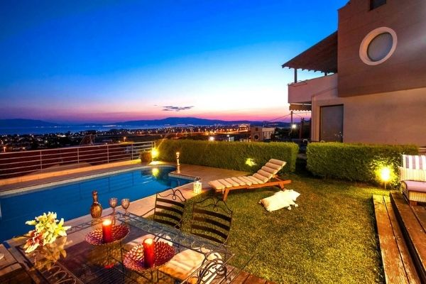 blue clean swimming pool at sunset with view of water