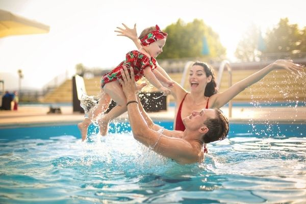 clean inground pool with happy family swimming
