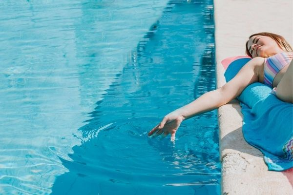 woman lying next to clean pool dipping hand in water