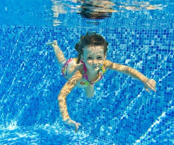 child swimming in pool underwater blue tiles